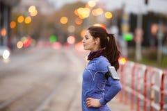 运行在城市的蓝色运动衫的少妇 免版税库存图片