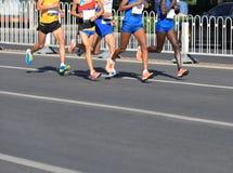 运行在城市的马拉松运动员 免版税库存照片