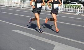 运行在城市的马拉松运动员 免版税图库摄影