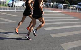 运行在城市的马拉松运动员 图库摄影