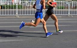 运行在城市的马拉松运动员 免版税库存图片