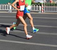 运行在城市道路的赛跑者 免版税库存图片