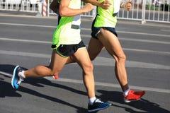 运行在城市道路的赛跑者 免版税库存照片