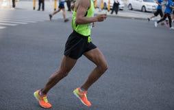 运行在城市道路的马拉松运动员 库存图片