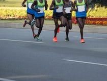 运行在城市道路的马拉松运动员 免版税图库摄影