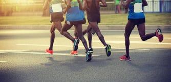 运行在城市道路的马拉松运动员 免版税库存照片