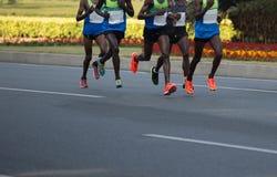 运行在城市道路的马拉松运动员 免版税库存图片