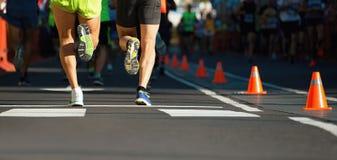 运行在城市道路,在腿的细节的马拉松运动员 免版税库存图片