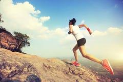 运行在山峰的妇女赛跑者 免版税库存照片