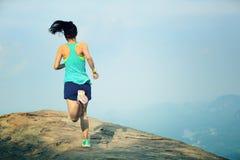 运行在山峰的妇女赛跑者 免版税库存图片