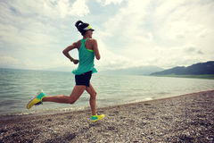 运行在日出海边足迹的赛跑者 库存照片