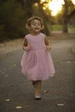 运行在日落的桃红色礼服的珍贵的ittle女孩 图库摄影