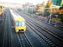 运行在最快速度行动图象的轨道的黄色火车 免版税库存图片