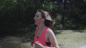 运行在有做锻炼的训练的身体的森林亭亭玉立的妇女的桃红色衬衣的可爱的嬉戏女孩 耳机的女孩是brea 影视素材