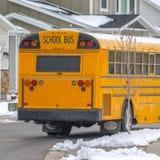 运行在有新鲜的雪的一条路的一黄色学校班车的正方形背面图在冬天 库存图片