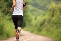 运行在森林足迹的妇女赛跑者 免版税库存图片