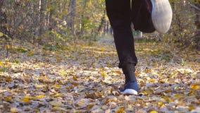 运行在森林道路的坚强男人的腿盖用色的叶子 跨步在干燥落叶的人凹凸部 运动员 影视素材