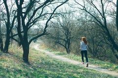 运行在森林,早期的春天的幼小健身妇女足迹赛跑者,那里是在树的没有叶子  库存照片
