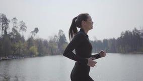 运行在河岸的运动服的可爱的亭亭玉立的妇女 E ?? 保留她的身体的夫人  股票视频
