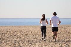 运行在海滩的男人和妇女 免版税库存照片