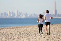 运行在海滩的男人和妇女 免版税库存图片