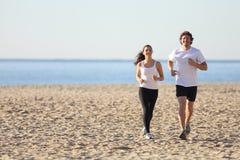 运行在海滩的男人和妇女 免版税图库摄影