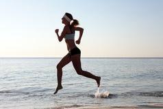 运行在海滩的美丽的新体育运动妇女 库存图片