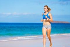 运行在海滩的美丽的运动妇女 免版税库存照片