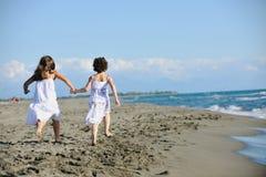 运行在海滩的逗人喜爱的小女孩 库存照片