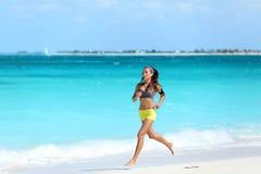 运行在海滩-夏天锻炼的妇女赛跑者 库存图片