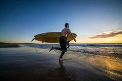 运行在海滩的冲浪者 免版税库存图片