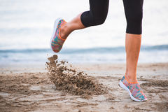 运行在海滩的女性腿特写镜头在日出在与沙子行动的早晨 库存图片