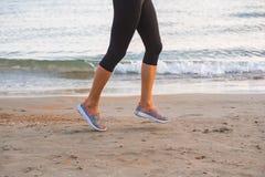 运行在海滩的女性腿特写镜头在日出在早晨 免版税图库摄影