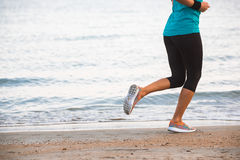 运行在海滩的女性腿特写镜头在日出在早晨 免版税库存照片