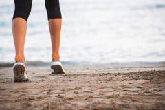 运行在海滩的女性腿特写镜头在日出在早晨 免版税库存图片