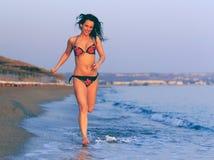 运行在海滩的泳装的愉快的妇女 免版税库存图片