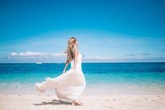 运行在白色沙子海滩的长的白色礼服的美丽的白肤金发的长的头发新娘 背景的热带turquois海 库存照片