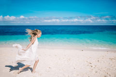 运行在白色沙子海滩的长的白色礼服的美丽的白肤金发的长的头发新娘 图库摄影