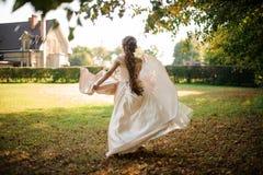 运行在秋天公园的一白色婚纱的美丽的新娘 免版税库存照片