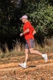运行在红色T恤杉的年轻赛跑者在春天 图库摄影