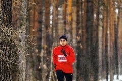 运行在落的雪的幼小公赛跑者在森林里 免版税图库摄影