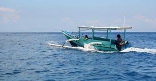 运行在蓝色海的一条木小船在Gili Meno,印度尼西亚 库存图片