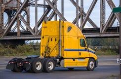 运行在路的明亮的黄色大半船具卡车拖拉机在老捆铁路桥梁下 免版税库存照片