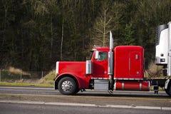 运行在路的经典强有力的红色大半船具卡车与 库存照片