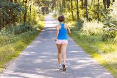 运行在路的运动的少妇赛跑者 免版税图库摄影