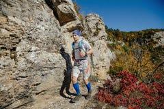 运行在轨道的公赛跑者在岩石和秋天森林旁边 库存图片