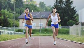 运行在运动跑道的二个女孩 免版税图库摄影