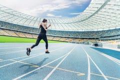 运行在连续轨道体育场的运动服的健身妇女 免版税图库摄影