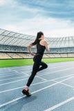 运行在连续轨道体育场的运动服的健身妇女 免版税库存图片