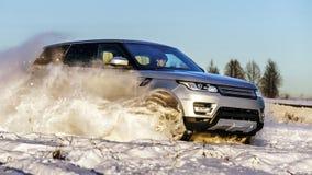 运行在雪原的强有力的4x4 offroader汽车 免版税库存照片
